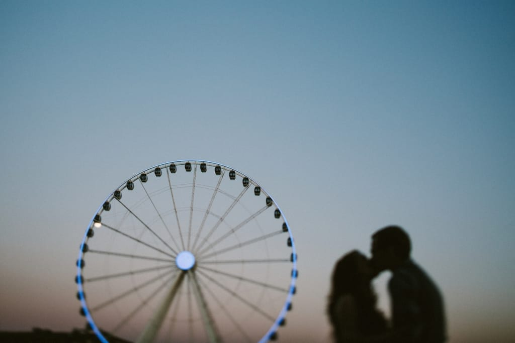 couple kissing at the seattle waterfront with ferris wheel in the background