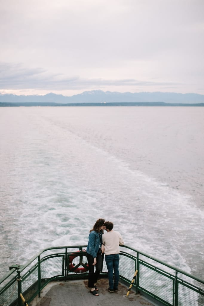 couple kissing on the seattle ferry with sweeping views of the water and mountains