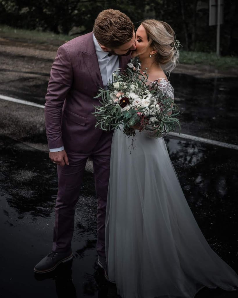 groom kissing a bride holding a bouquet with burgundy, white, and blush flowers, and greenery