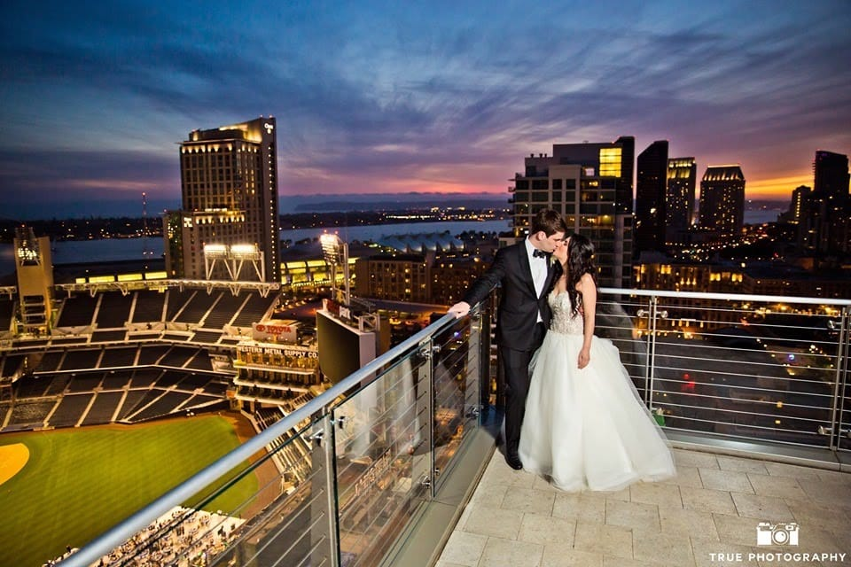 newly married couple kissing on the terrace of diamond view tower with the san diego skyline and sunset in the background