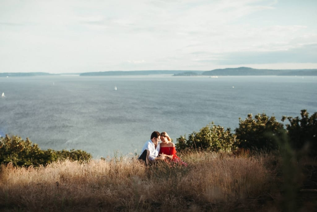 engaged couple sitting in a field of tall grass at discovery park in seattle with mountains in the background