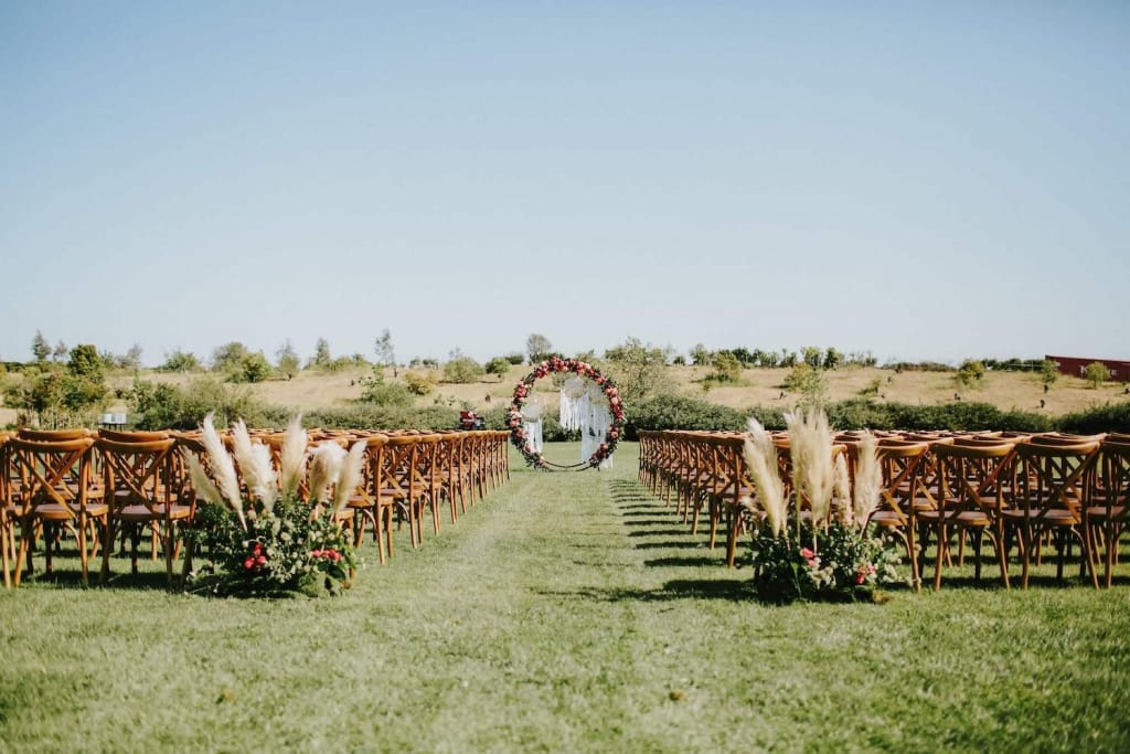 a circular wedding arch covered in flowers, and chairs set up for a wedding, on a grassy field