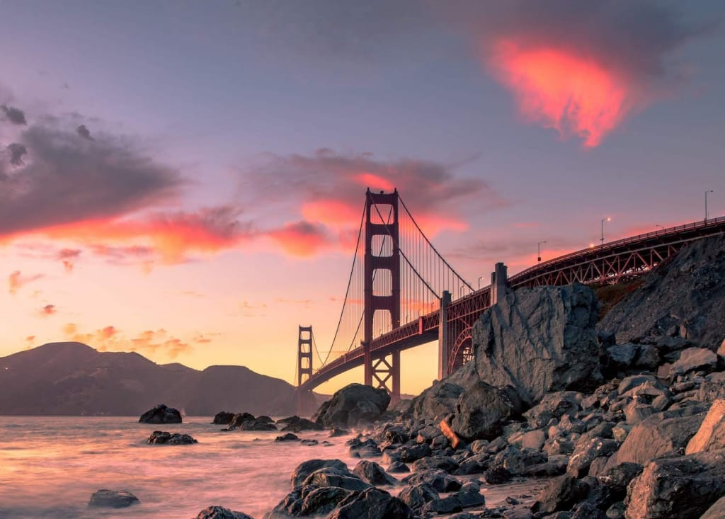 baker beach in san francisco, california with the golden gate bridge in the background at sunset