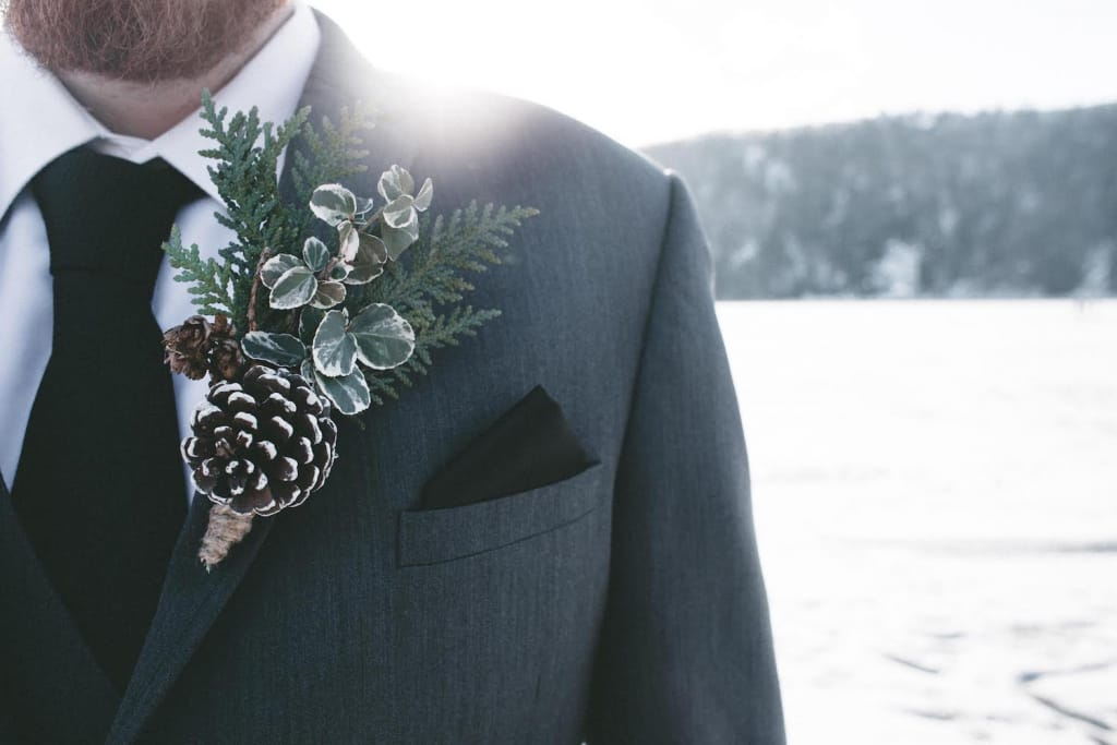 groom wearing a boutonniere made out of cedar greenery and pinecones