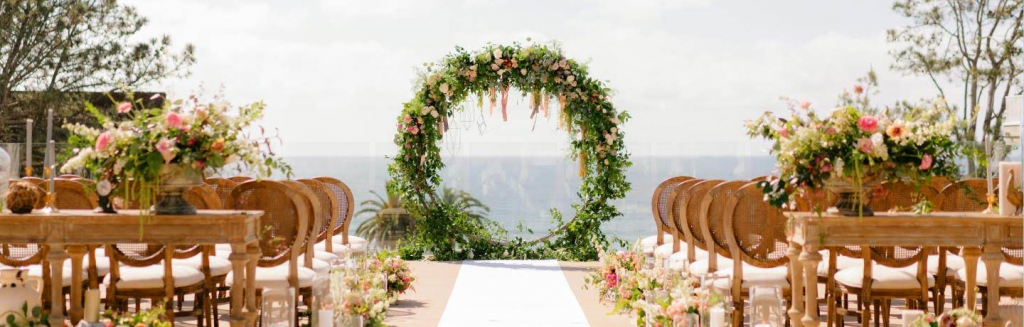 floral displays and chairs set up for a wedding on the deck of l'auberge del mar in san diego