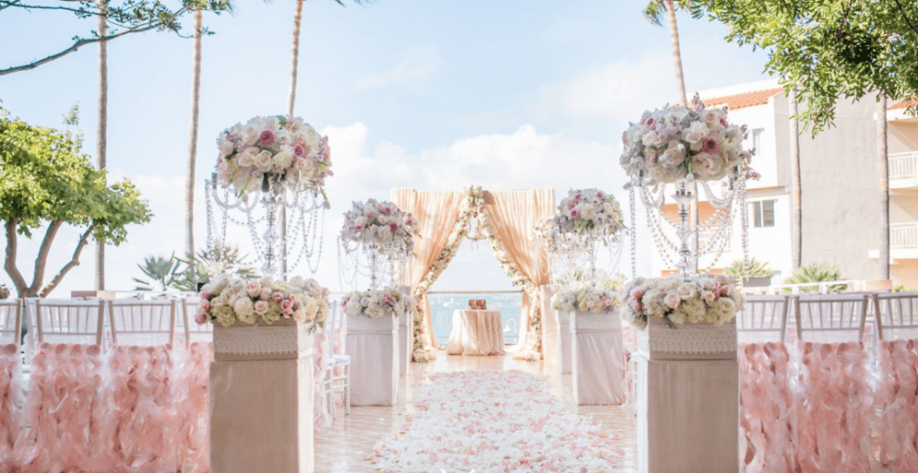 an outdoor setup for a wedding ceremony at loews coronado bay resort with pink and white flowers and chairs