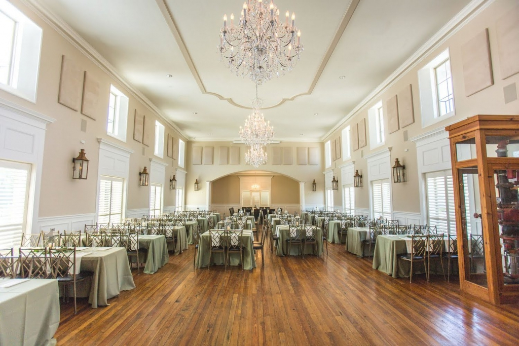 interior of the Grande Ballroom in the Milltown Historic District in New Braunfels, with three chandeliers shining down on tables set for a wedding reception