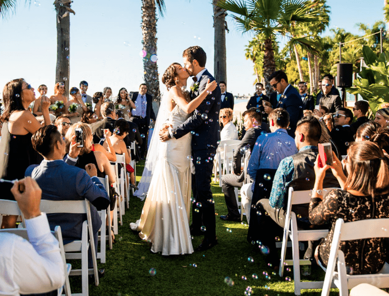 bride and groom kiss as they walk down the aisle at wedding ceremony in paradise point in san diego