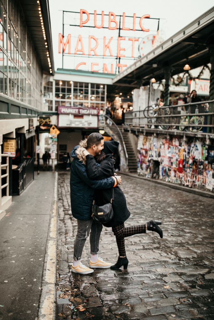 couple hugging at pike place market in seattle on a rainy day