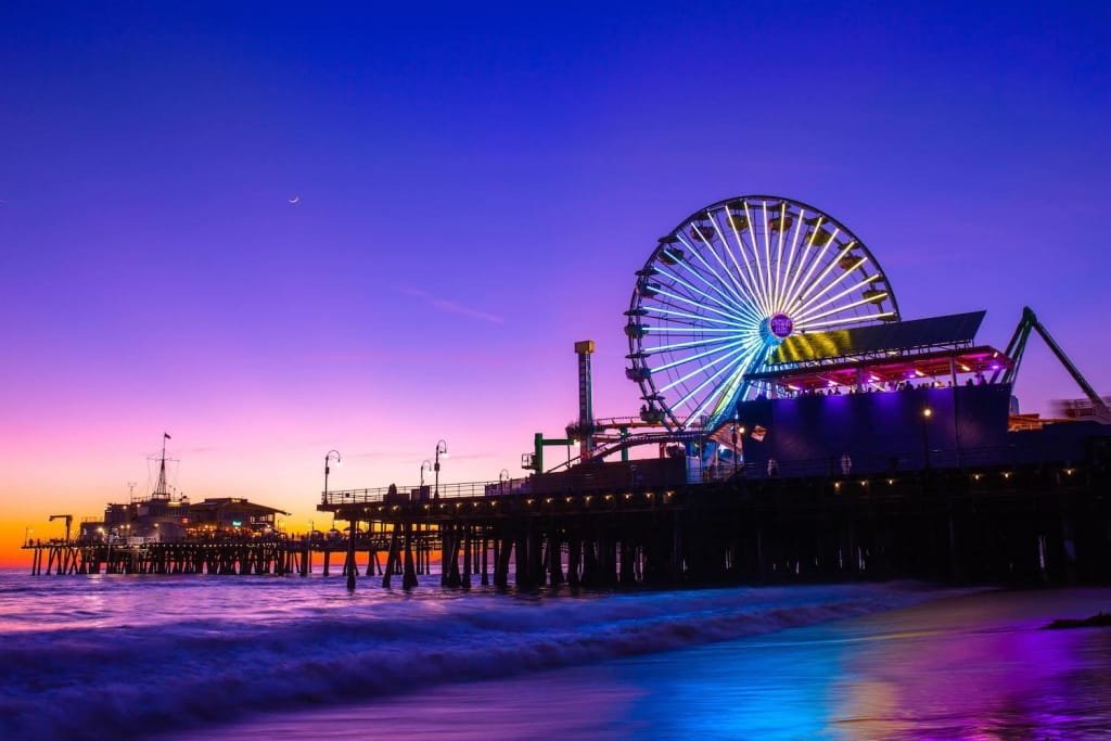 santa monica pier ferris wheel lit up during a purple, pink, and orange sunset in california