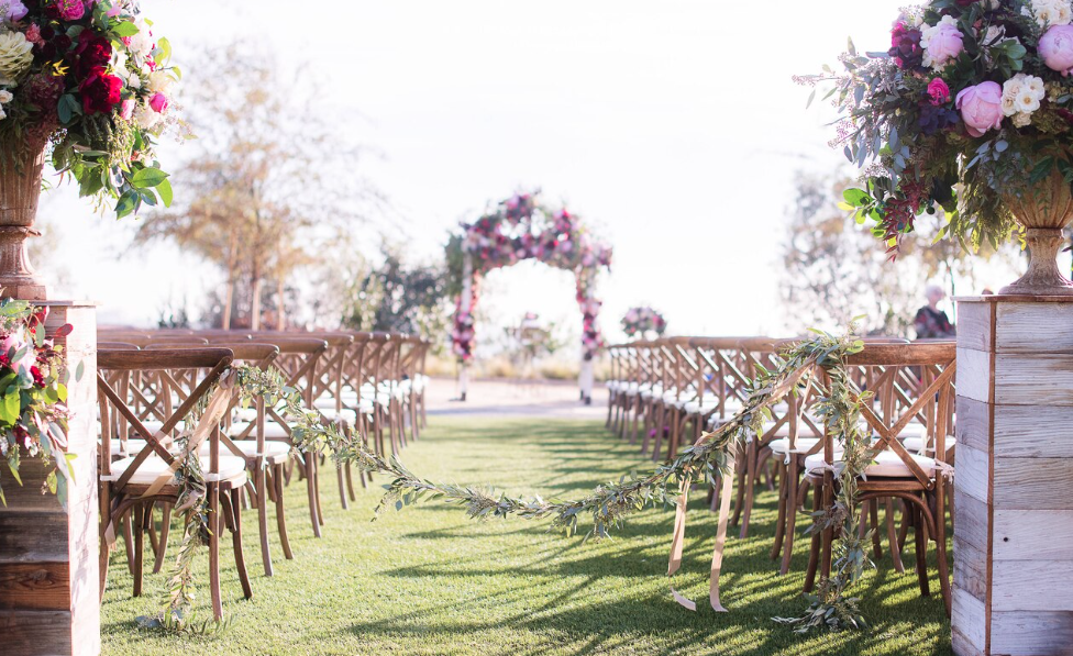 a flower-covered arch and chairs set up on a manicured lawn for a wedding at sheraton carlsbad resort & spa