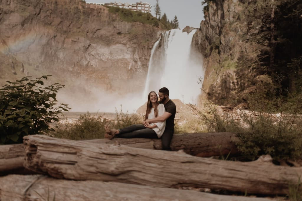 couple embracing at snoqualmie falls in seattle with waterfall in the background