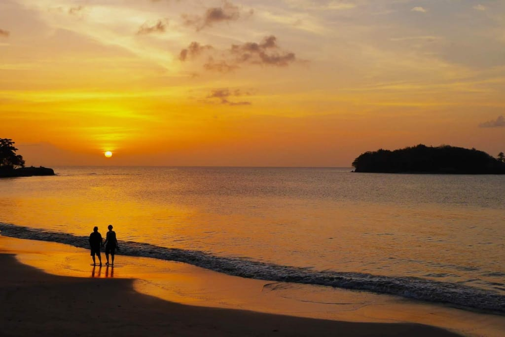 two people walking on the beach during an orange sunset in Castries, St. Lucia