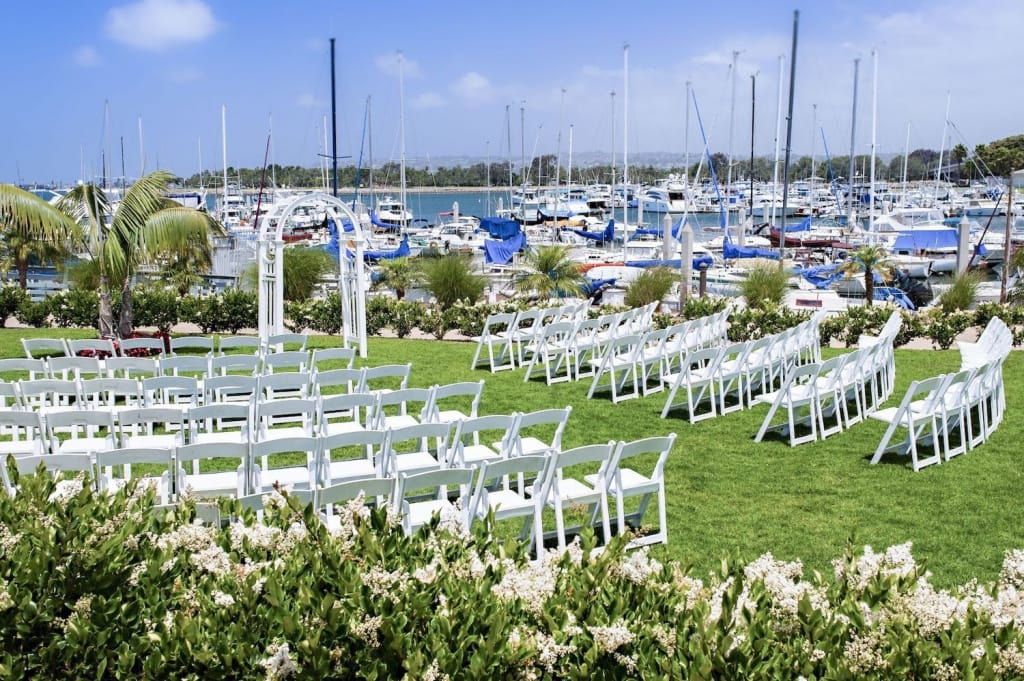 white chairs set up for a wedding on a green lawn overlooking the marina at the dana on mission bay