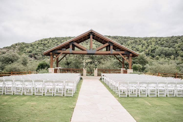 large wooden open-air pavilion at the end of a stone path surrounded by white wedding chairs on a grass lawn