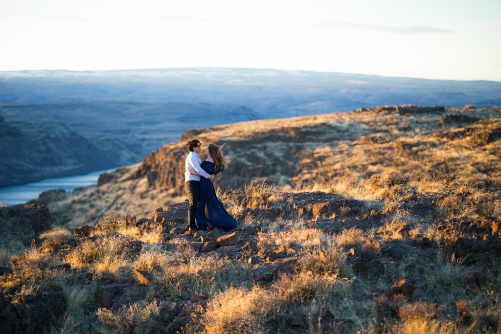 couple embracing on a cliff at vantage in seattle with sweeping views of the water