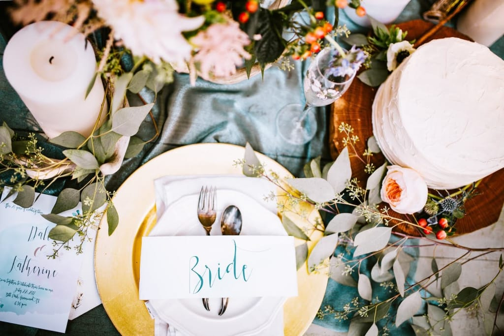 table setting at winter wedding reception with a blue table cloth, and white candles, red berries, and eucalyptus sprigs on the table