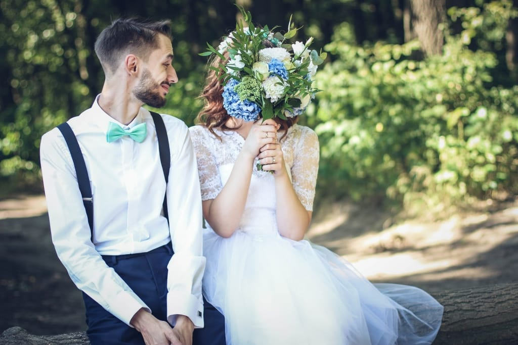 Groom and bride playfully covering her face with a blue-and-white floral bouquet