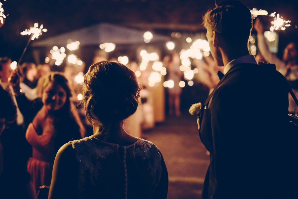 Bride and groom walking with wedding guests holding sparklers