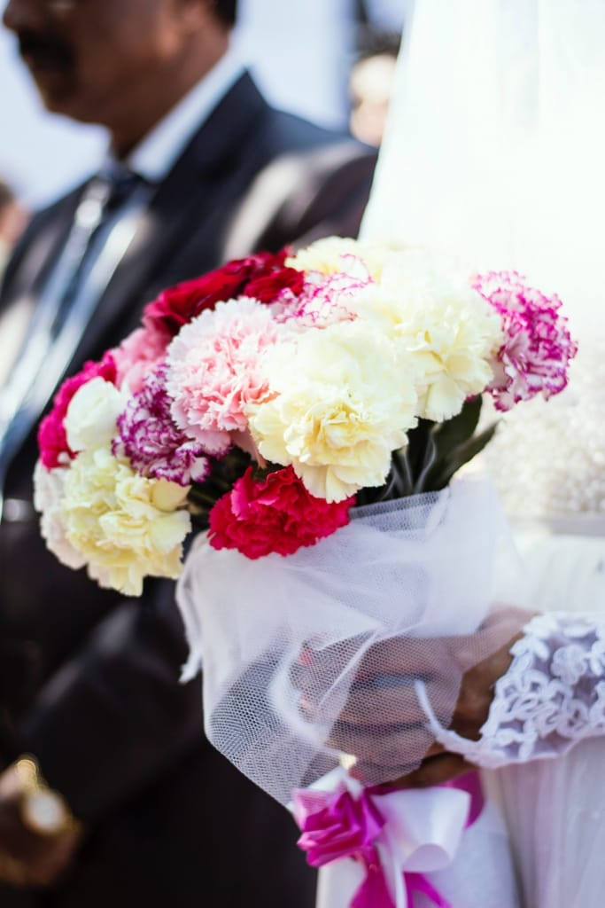 bride holding bouquet of carnations