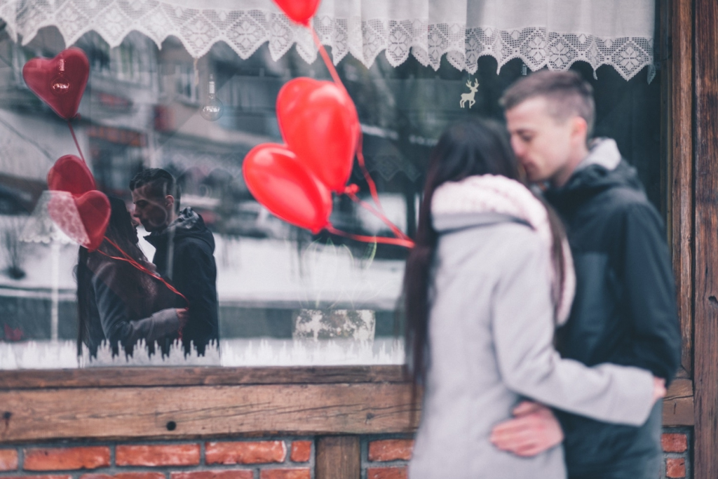 man and woman embrace outside store window showing their reflection and Valentine's Day balloons