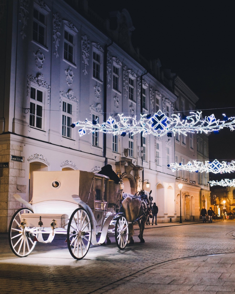white horse drawn carriage rides through the city at night