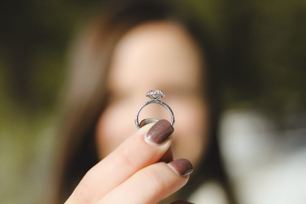 woman out of focus holding up engagement ring