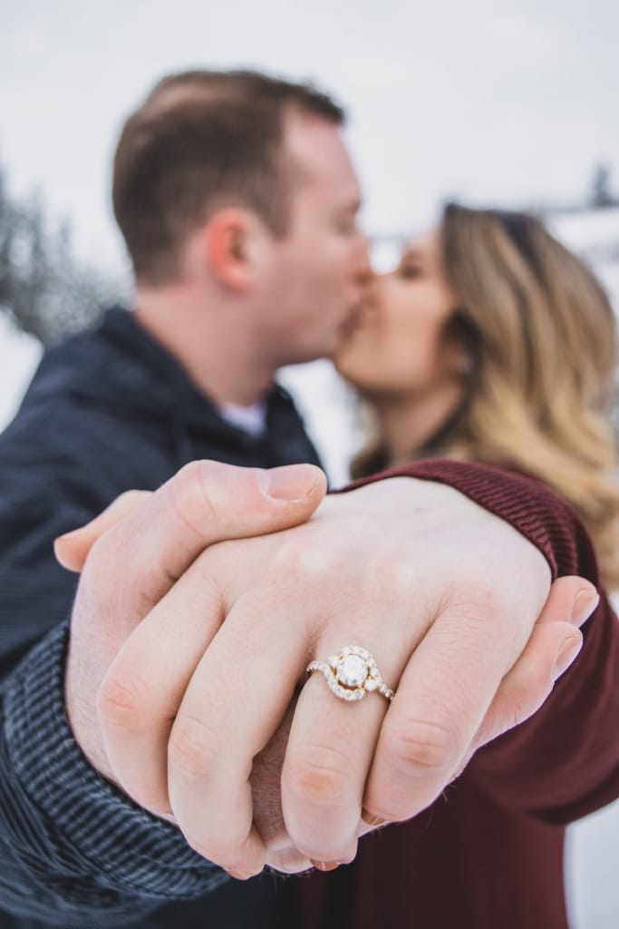 man and woman kiss while holding up engagement ring