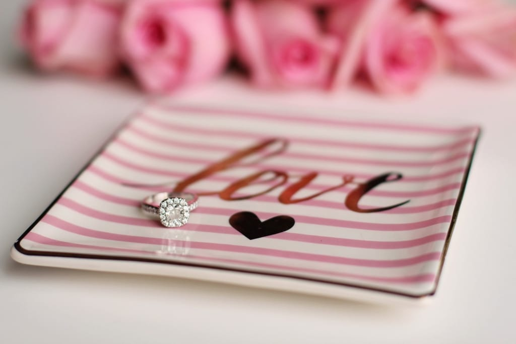 sparkly engagement ring sitting on a pink-striped plate that says love