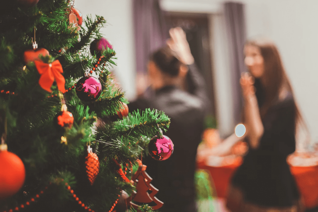 Close-up photo of Christmas tree with blurred couple in background