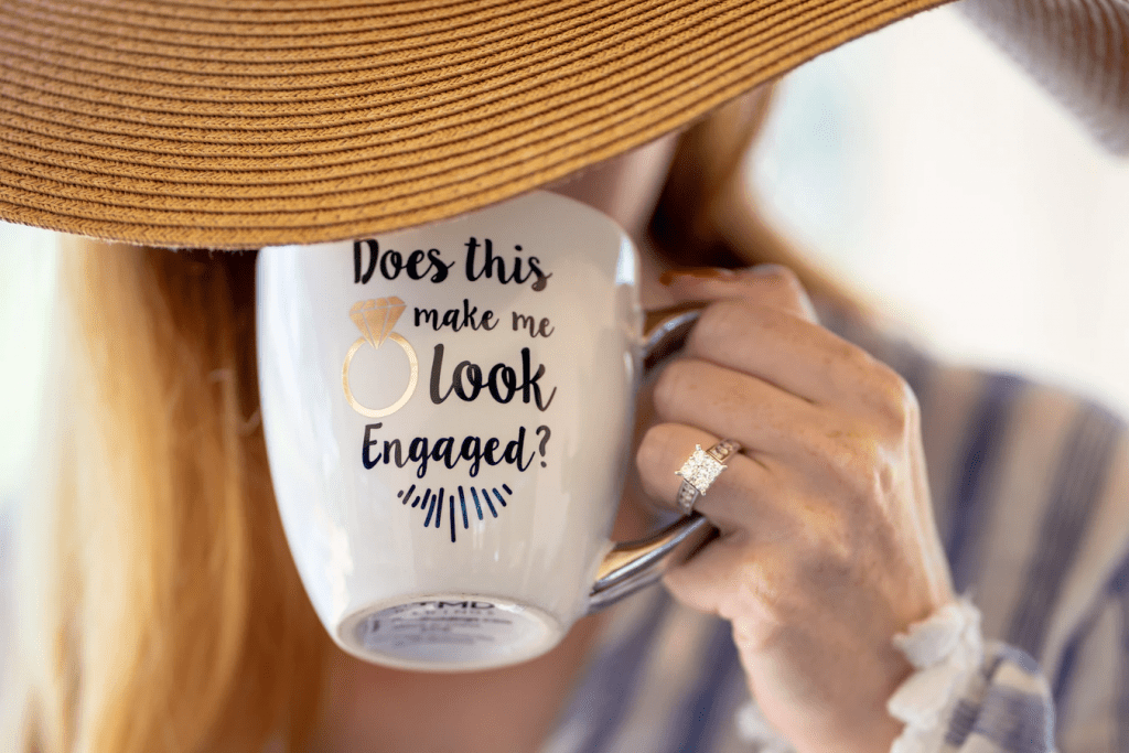 Close-up of woman with diamond engagement ring holding a mug