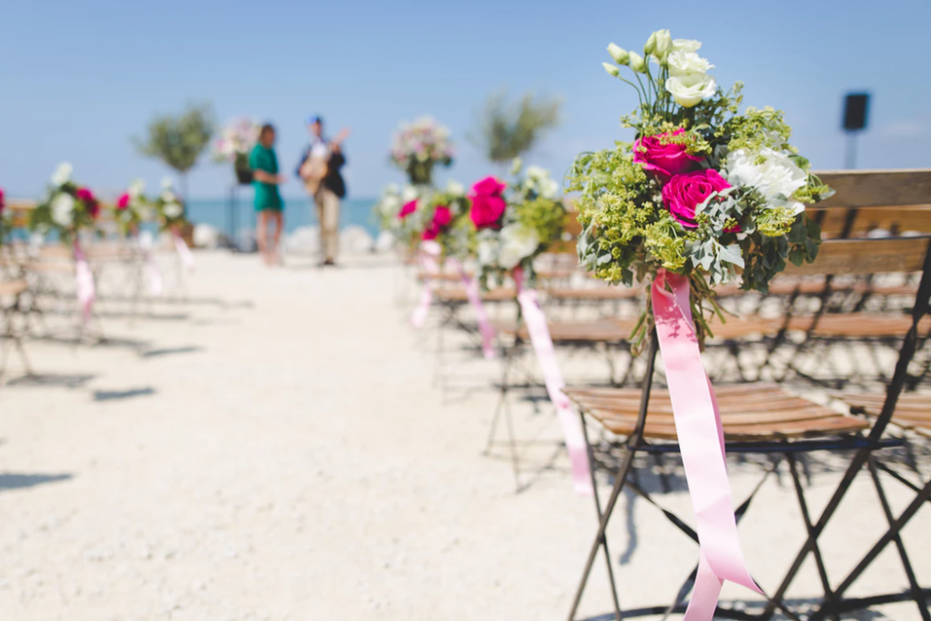 Pretty beach wedding featuring wood chairs decorated with bright flowers