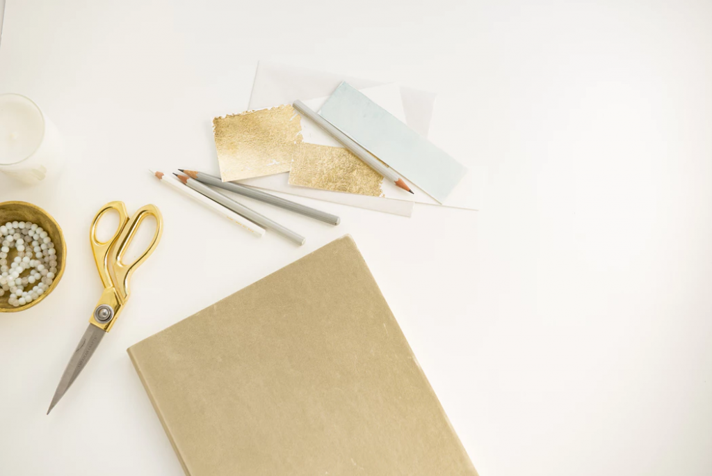 When to send save-the-dates: Gold foil paper, scissors, and pencils