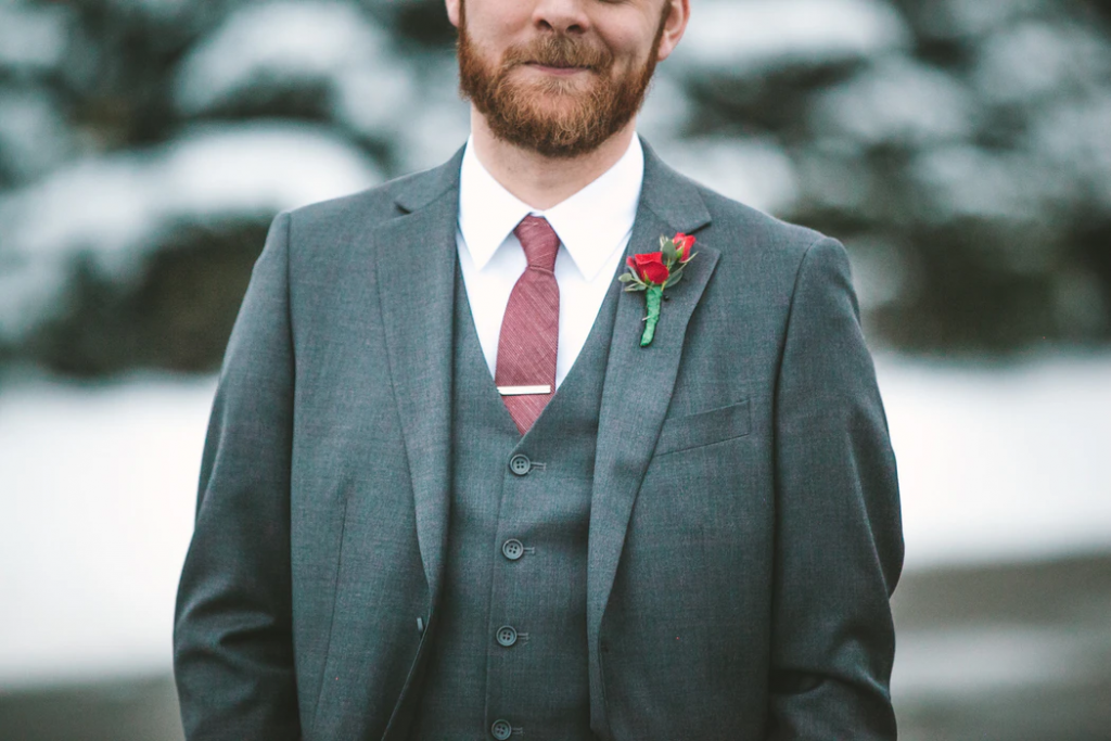 Groomsman with red rose on lapel