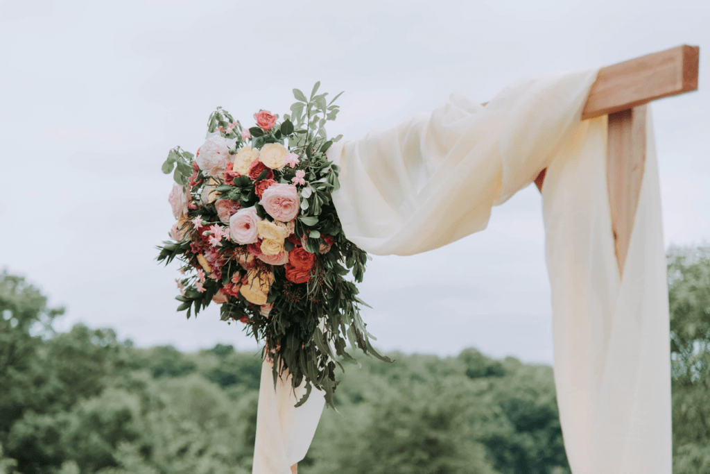 Lovely floral arrangement on a wooden beam with draped fabric