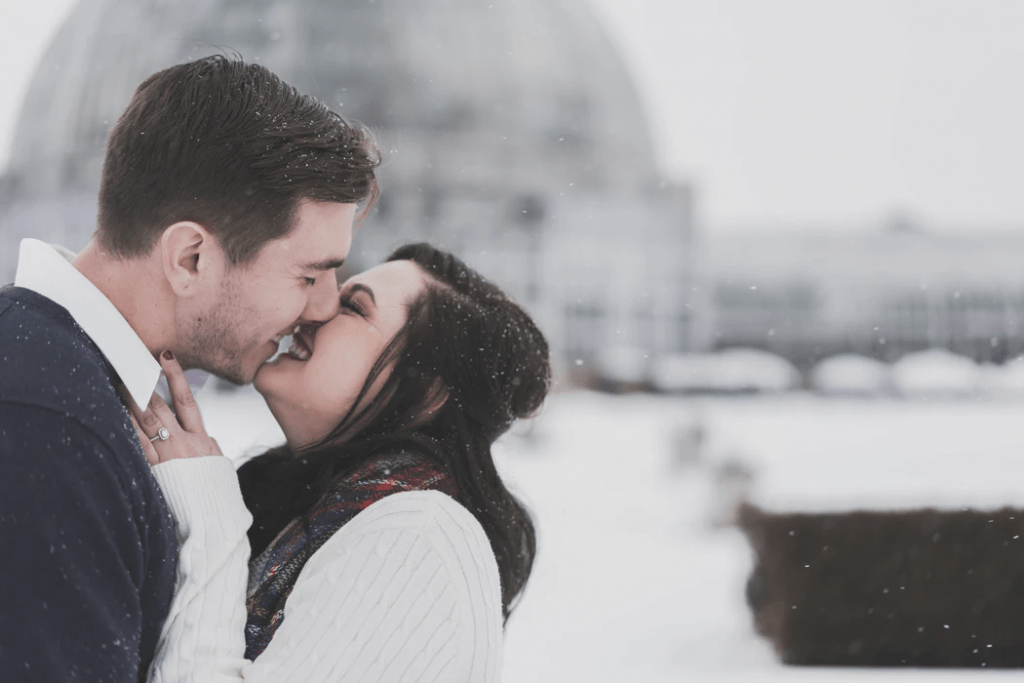 Couple smiling and kissing in the snow