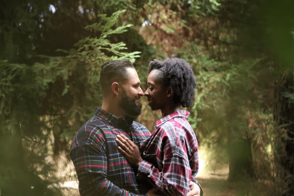 Happy couple looking into each other's eyes with forest background