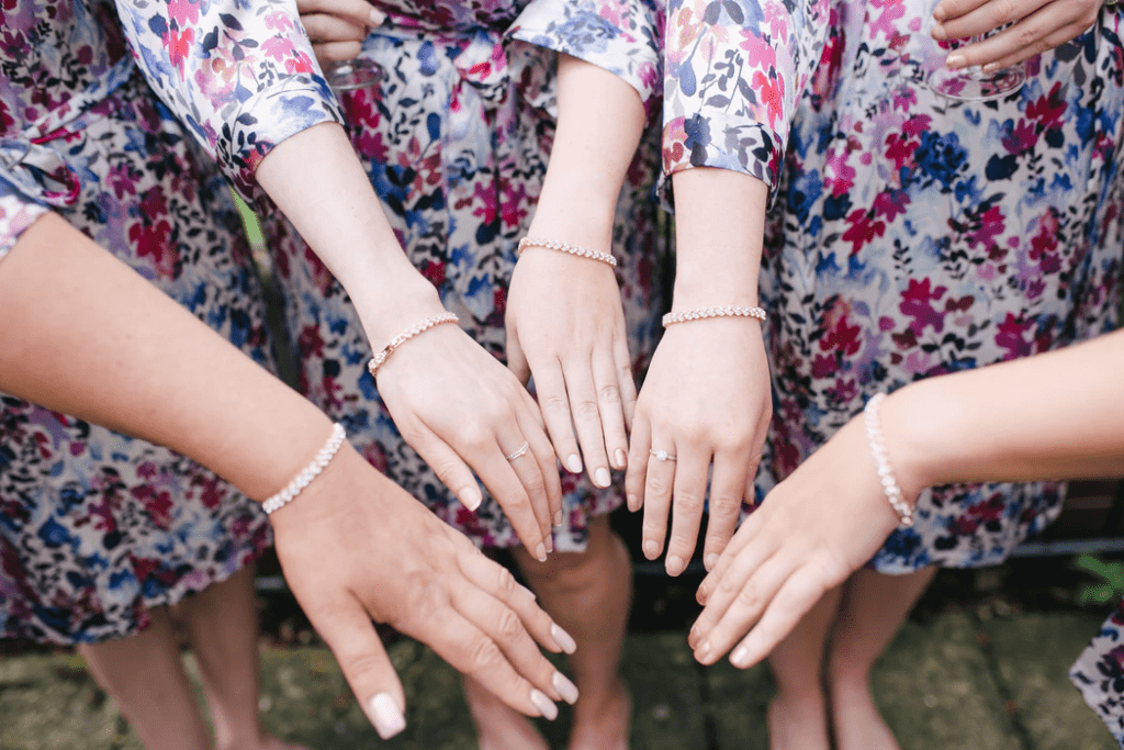 Close-up photo of bridesmaids arms with matching bracelets