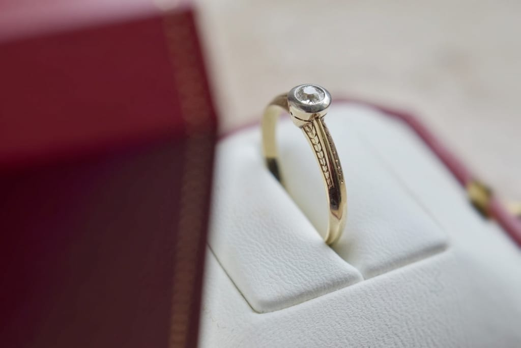 gold engagement ring in red box