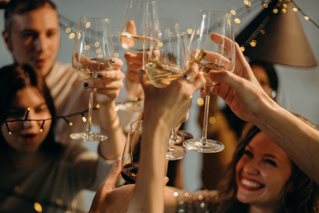 people clinking champagne flutes at a party
