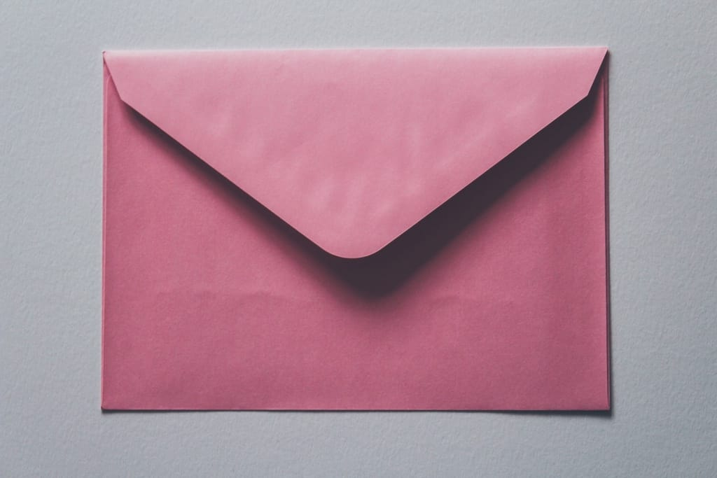 pink envelope on plain grey background