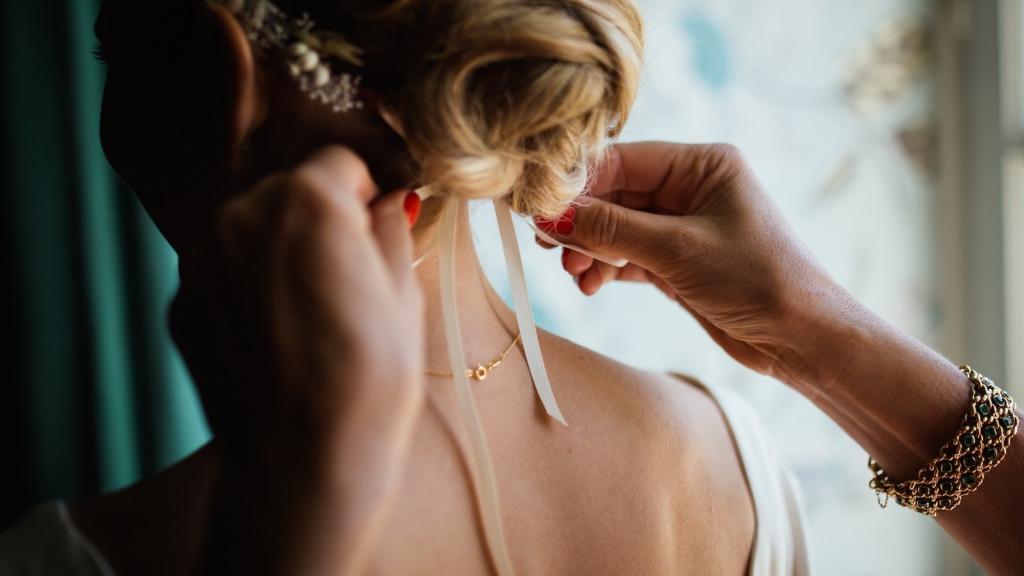 woman tying a white ribbon around bride's hair