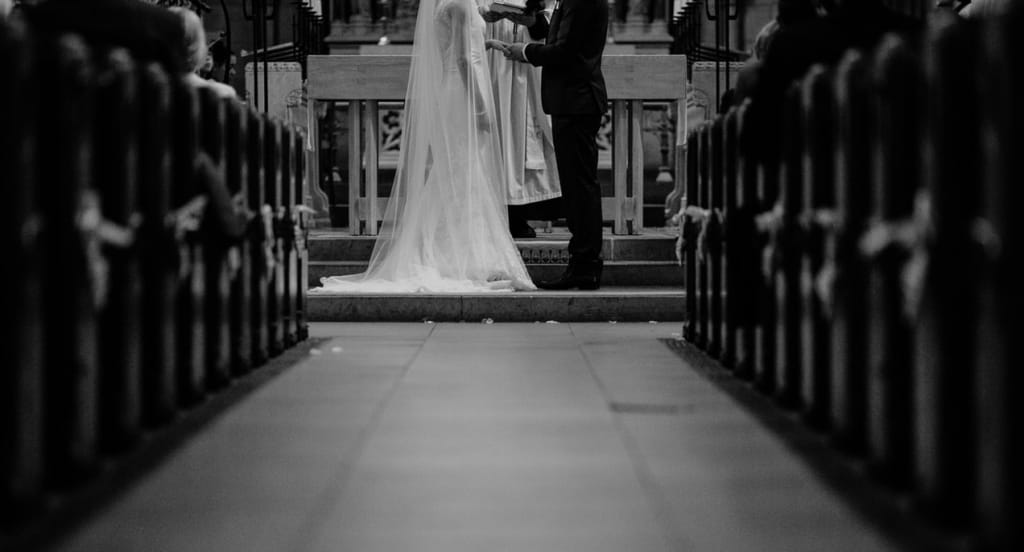 Wedding ceremony script: Black and white photo of couple at the church altar