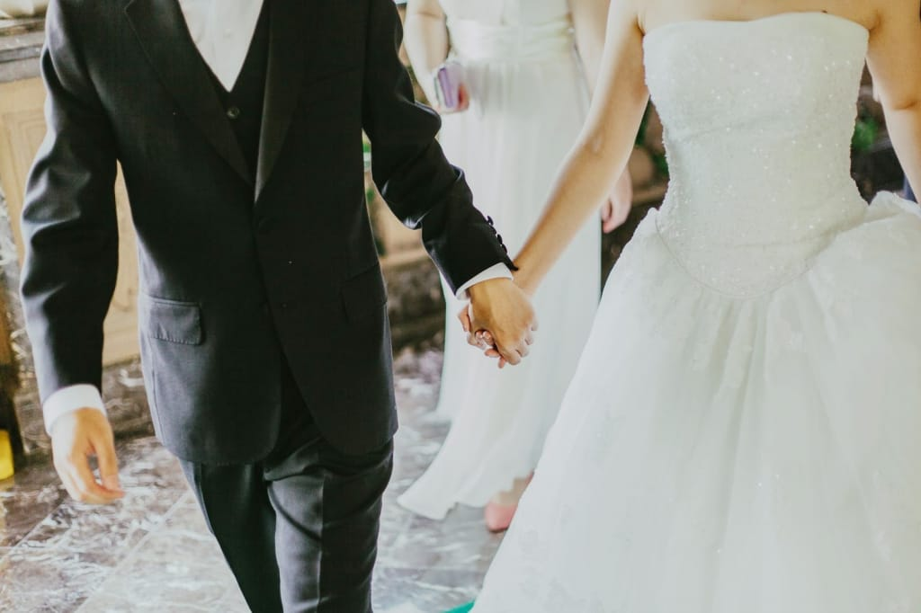 Close-up shot of bride and groom holding hands